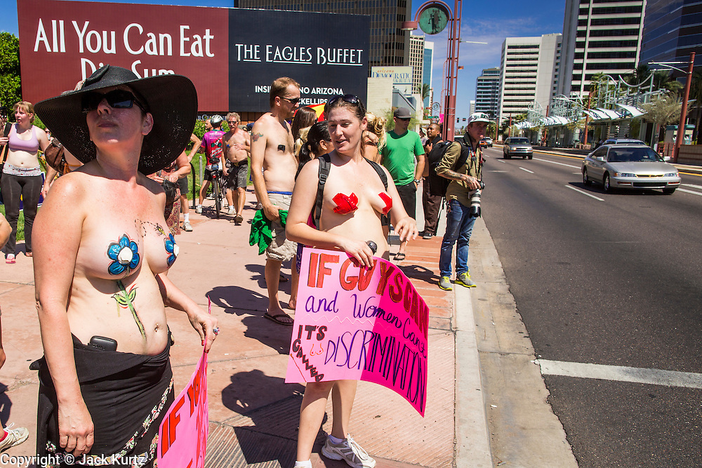 26 MARCH 2012 - PHOENIX, AZ: CHRISTI, left, and KELLY CAYE, and other topless protesters wait to cross a Phoenix street Sunday. About 40 people marched through central Phoenix Sunday to call for a constitutional amendment to give women the same right to go shirtless in public that men have. The Phoenix demonstration was a part of a national Topless Day of Protest. Phoenix prohibits women from going topless in public so protesters, women and men, covered their nipples and areolas with tape. The men did it to show solidarity with the women marchers.    PHOTO BY JACK KURTZ