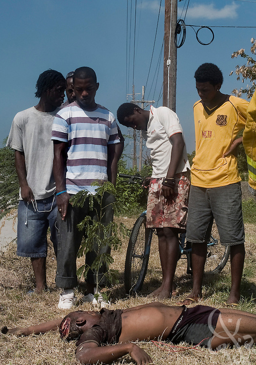 Onlookers stand above the body of a young, male murder victim found dumped in a gully in Meadowbrook Estate neighborhood of Kingston, Jamaica June 13, 2008. On average there is a murder every 5.5 hours in Jamaica, an astronomical rate given the total population of the tiny Caribbean nation is only around 3 million.