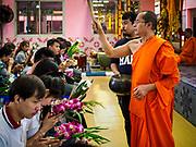 """30 DECEMBER 2017 - BANG KRUAI, NONTHABURI, THAILAND:  A Buddhist monk leads a prayer at Wat Ta Khien, about 45 minutes from Bangkok in Nonthaburi province. The temple is famous for the """"floating market"""" on the canal that runs past the temple and for the """"resurrection ceremonies"""" conducted by monks at the temple.      PHOTO BY JACK KURTZ"""