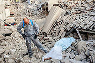 24 August 2016, Amatrice Italy - A rescuer beside the lifeless body of a man pulled from the rubble covered with a sheet after a 6.3 earthquake hit the town of Amatrice in Lazio region killing more than 240 people. Many other towns of the italian central regions have been hit by the quake. There are still many missing people under the rubble.