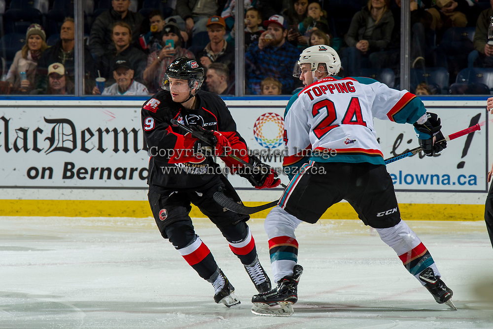 KELOWNA, CANADA - JANUARY 4: Tyson Upper #9 of the Prince George Cougars checks Kyle Topping #24 of the Kelowna Rockets  on January 4, 2019 at Prospera Place in Kelowna, British Columbia, Canada.  (Photo by Marissa Baecker/Shoot the Breeze)