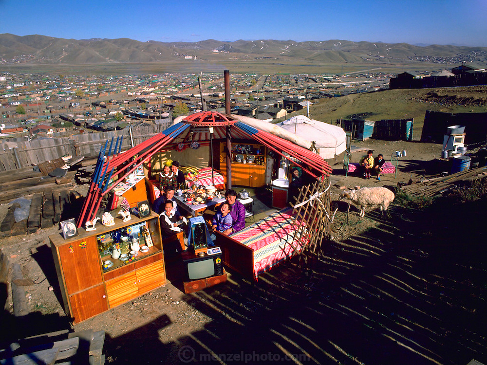 The Regzen family outside their ger with all of their possessions, Ulaanbaatar, Mongolia. Published in Material World pages 40-41. The Regzen Batsuuri family lives in a 200 square foot ger (round tent built from canvas, strong poles, and wool felt) on a hillside lot overlooking one of the sprawling valleys that make up Ulaanbaatar, Mongolia. They live in a squatter's area, as do thousands of other Mongols who moved here from the rural countryside.