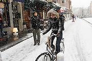 Een fietser rijdt door de sneeuw op de Vismarkt in Utrecht. <br /> <br /> A cyclist in the snow at the Vismarkt in Utrecht