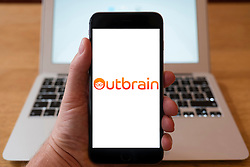 Using iPhone smartphone to display logo of Outbrain, an online advertiser specializing in presenting sponsored website links.