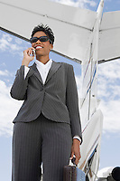 Mid-adult businesswoman using mobile phone in front of airplane.