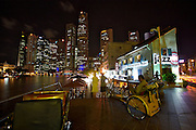 Nightlife along Singapore River. Trishaws waiting for tourists at Boat Quay.