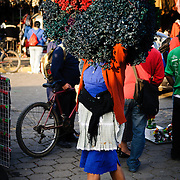 A woman carries red flowers on her head at the main market in Antigua, Guatemala.