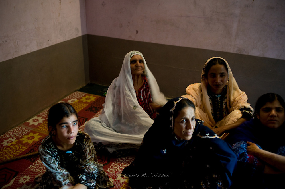 Dai Ghair Bibi sits among some of the female members of her family. She doesn't know her age and how many deliveries she assisted over the years, but most fondly remembers assisting the births of her family members. Karachi, Pakistan, 2011