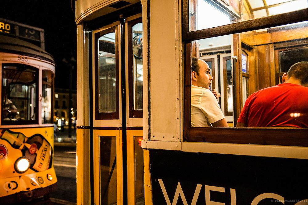Men inside a tram at night. Lisbon, Portugal
