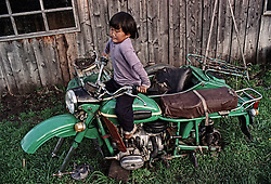 An altay girl seats on a motorcycle with sidecar attached on a deer-farm in the Altai (eastern Siberia) village of Mendur-Sokon, Russia, 22 July 2001. Local population traditionally sell pants (the young, just grown antlers of a deer) to farmacilogical factories, which produce extremely effective biological active medicine Pantacrin with high tonic effect. The antlers are sold by local people for about $150 per kilo, which cost up to $500 on Asian markets..