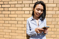 Smiling young businesswoman text messaging on cell phone against brick wall