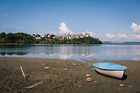 ANGUILLARA SABAZIA (LAKE BRACCIANO), ITALY - 26 JULY 2017: A view of a beached rowboat on a newly exposed earth in front of the town of Anguillara Sabazia on Lake Bracciano, whose level has dropped more than 1,50 meters recently, in Anguillara Sabazia (Lake Bracciano), Italy, on July 26th 2017.<br /> <br /> Lake Bracciano provides eight percent of Rome's water and has sunk about 1.5 meters<br /> <br /> A severe drought and sweltering temperatures have led Rome city officials to consider a potential rationing of drinking water for eight hours a day for a million and a half Rome residents. The water crisis has become yet another sign of man being at the mercy of an increasingly extreme climate, but also of once mighty Rome's political impotence, managerial ineptitude and overall decline.Lake Bracciano provides eight percent of Rome's water and has sunk about 1.5 meters<br /> <br /> A severe drought and sweltering temperatures have led Rome city officials to consider a potential rationing of drinking water for eight hours a day for a million and a half Rome residents. The water crisis has become yet another sign of man being at the mercy of an increasingly extreme climate, but also of once mighty Rome's political impotence, managerial ineptitude and overall decline.