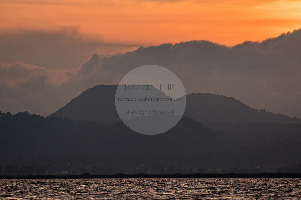 Sunset over the trans-volcanic belt of mountains in Lake Patzcuaro, Michoacan, Mexico.