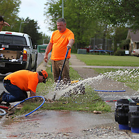 Terry Wilson, from left, Logan Tanner, Jacob Bailey and Danny Grubbs have to fix a broken water line before installing new water meters that transmit their readings remotely to a center location.