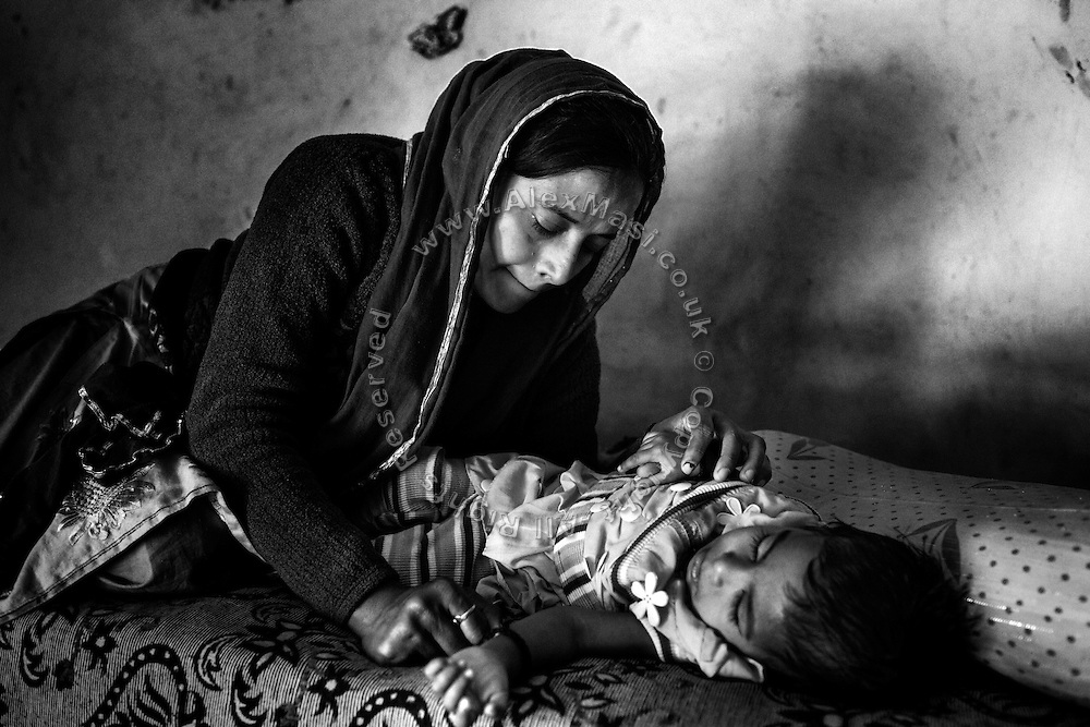 Shabana, 30, a '1984 Gas Survivor', is deep in thoughts while looking after her severely disabled young daughter, Sufiya, one and a half years old, while lying on a bed inside their home in Kabar Kana, Bhopal, Madhya Pradesh, central India. Sufiya is Shabana's first child and she is now scared of considering further pregnancies. Sufiya is affected by a neurological disorder causing severe seizures and slow brain development. She is not able to eat or swallow food naturally, and is living exclusively on water and milk.
