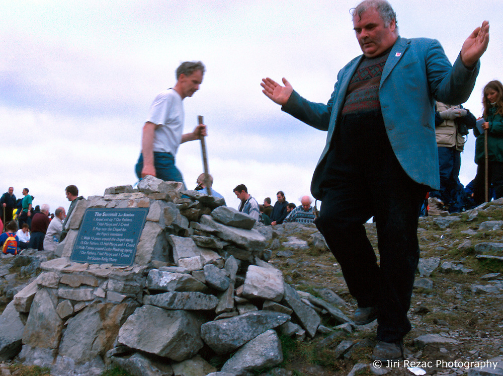 IRELAND CO. MAYO CORAGH PATRICK JUL99 - A pilgrim is occupied by devotional prayer on top of Croagh Patrick mountain in western Ireland. Around 25,000 people, some of which are bare-footed, participate in this pilgrimage to the top of Croagh Patick mountain on the last Sunday of July from where in 441 A.D. St. Patrick supposedly sent Ireland's reptiles to their doom. ..jre/Photo by Jiri Rezac..© Jiri Rezac 1999..Contact: +44 (0) 7050 110 417.Mobile: +44 (0) 7801 337 683.Office: +44 (0) 20 8968 9635..Email: jiri@jirirezac.com.Web: www.jirirezac.com..© All images Jiri Rezac 1999 - All rights reserved.
