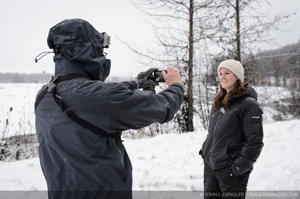 Dr. Scott Ford, avian veterinarian, Avian Speciality Veterinary Services of Alaska (left), uses his cell phone to film Rachel Wheat, a graduate student at the University of California Santa Cruz, for a field report of her describing her bald eagle research. Wheat is conducting a bald eagle migration study of eagles that visit the Chilkat River for her doctoral dissertation. She hopes to learn how closely eagles track salmon availability across time and space. The bald eagles are being tracked using solar-powered GPS satellite transmitters (also known as a PTT - platform transmitter terminal) that attach to the backs of the eagles using a lightweight harness. Information about Wheat's bald eagle migration study and the latest updates on the locations of the bald eagles she is tracking can be found on the Ecology Alaska website http://www.ecologyalaska.com . Social media and education outreach are an important part of of Wheat's project. Wheat along with Yiwei Wang, graduate student, University of California Santa Cruz and Dr. Taal Levi, wildlife ecologist, Cary Institute of Ecosystem Studies funded their various Alaska research projects through an innovative Kickstarter fundraising campaign. During late fall, bald eagles congregate along the Chilkat River to feed on salmon. This gathering of bald eagles in the Alaska Chilkat Bald Eagle Preserve is believed to be one of the largest gatherings of bald eagles in the world.