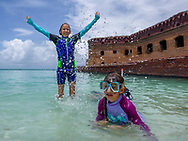 Kids enjoy the clear and calm water at Dry Tortugas National Park. Sisters splash in the zero-entry easy snorkeling zone beside Fort Jefferson. Model released photo.