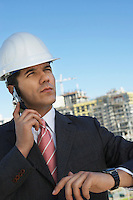 Businessman in hardhat using mobile phone, outdoors