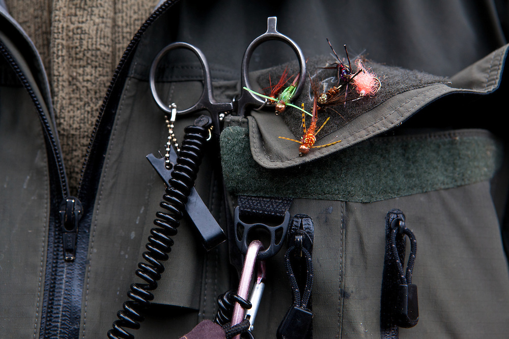 close up of anglers jacket and fishing tools