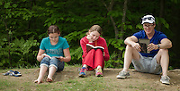 5th graders Taylor Hough and Jaylynn Fleury along with Gregg Hough read together quietly on a knoll at Woodland Heights Elementary School during Friday's BBQ and Read In.  (Karen Bobotas/for the Laconia Daily Sun)
