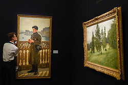 """© Licensed to London News Pictures. 02/06/2017. London, UK. A technician reviews (L to R) """"Portrait of Yuri Repin by the Bay of Naples"""", 1894, by Ilya Repin (Est. GBP 0.7-1m) and """"Summer"""", 1891, by Isaak Levitan (est. 1-1.5m).  Preview of Sotheby's sale of Russian pictures and works of art which takes place on 6 June 2017 at Sotheby's in New Bond Street. Photo credit : Stephen Chung/LNP"""
