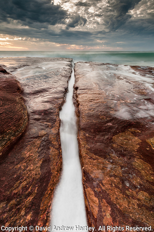 Water recedes through a rocky trough to the Indian ocean, Kalbarri, Australia
