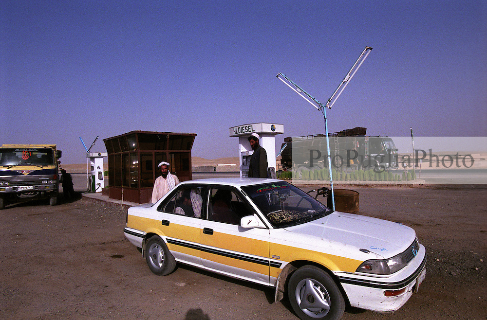 On the road to Kandahar a taxi, locally called just Corolla, is  parked at a petrol station for fuel.