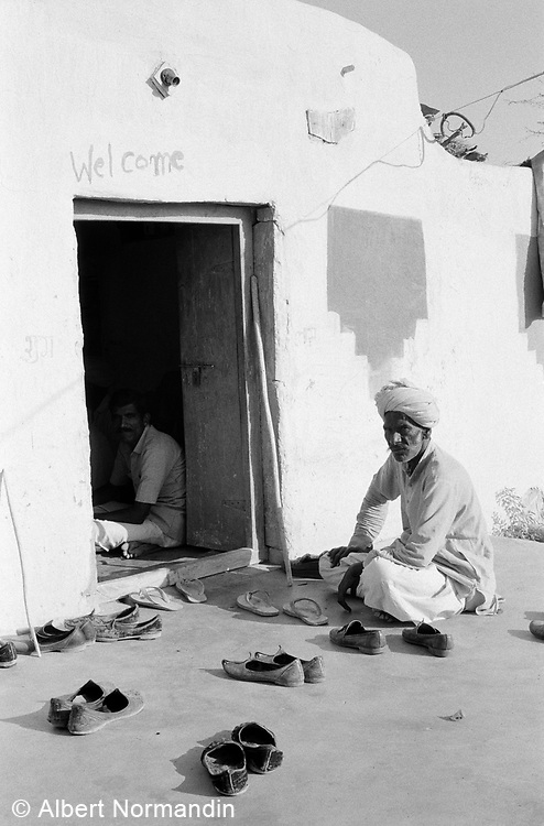 Man and shoes sitting outside of Men's Club entrance, Khuri village