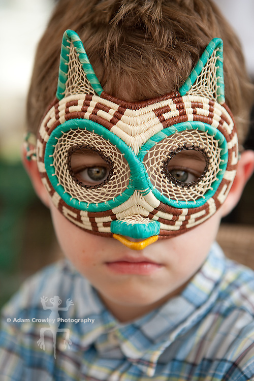 Boy (6 years old) wears a woven owl mask.
