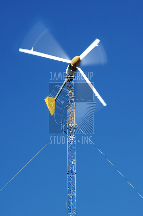 electric wind turbine generator spinning against blue sky