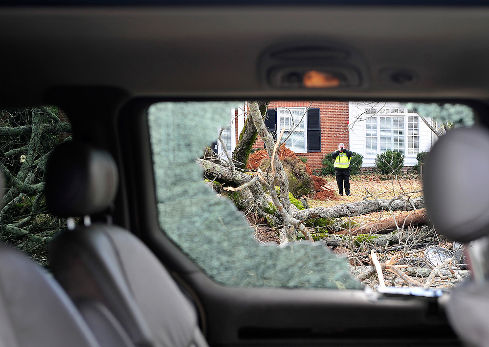 Athens-Clarke Emergency Managament Coordinator Chuck Gulley  is framed in the broken window of Peter Fancher's van as he takes a photo of a large oak tree that fell across Milledge Avenue near Oakland Avenue on Wednesday, Jan. 26, 2011 in Athens, Ga.  Fancher's window was broken by a limb from the falling tree.