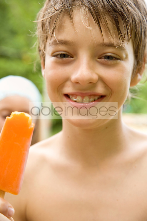Young Boy eating orange ice-lolly