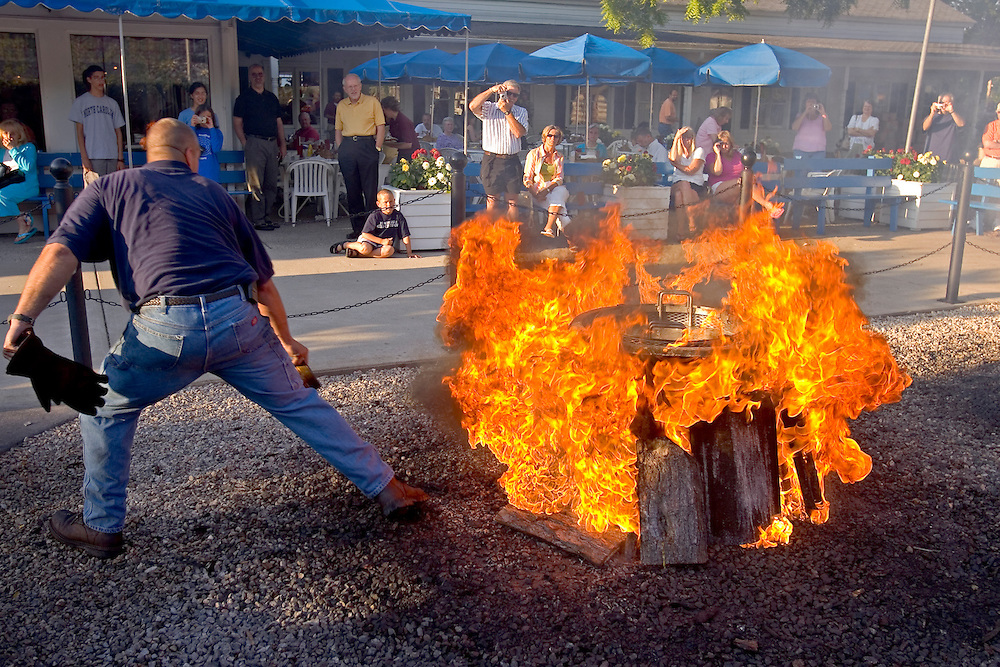 A boil master throws fuel on the fire of a fish boil to do the boil over at Pelletier's Restaurant in Fish Creek in Door County, Wisconsin.  (Mike Roemer Photo)