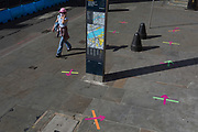 Ten weeks after the UK went into Coronavirus pandemic lockdown, the Office for National Statistics reveal that the total death toll has passed 50,000 covid-19 victims, a lady wearing a face mask walks past social distancing markings on the pavement outside a Post Office in the borough of Southwark which ensure queues of daytime customers keep to within lockdown rules, on 2nd June 2020, in London, England.