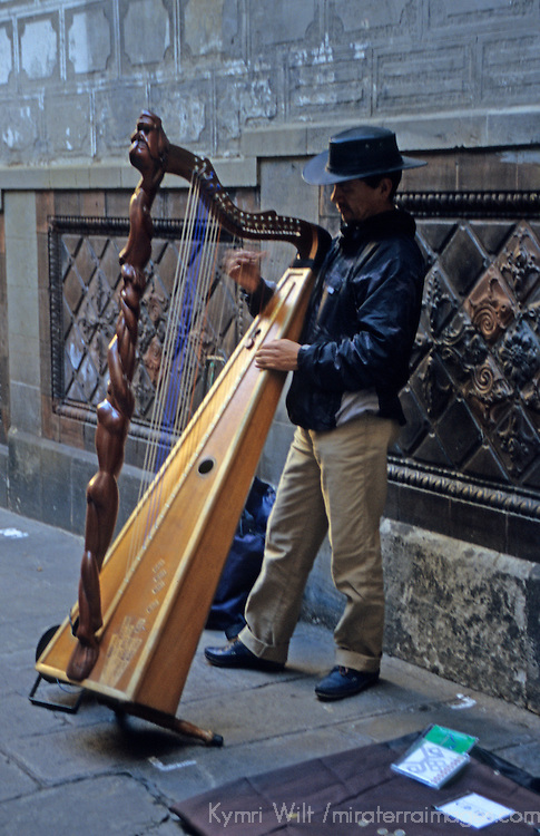 Europe, Spain, Barcelona. Street musician plays harp in the Gothic Quarter.