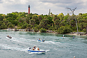 Paddle boarders and boats travel along the Indian River past the Jupiter Inlet Lighthouse at the South Beach Bridge in Jupiter, Florida.