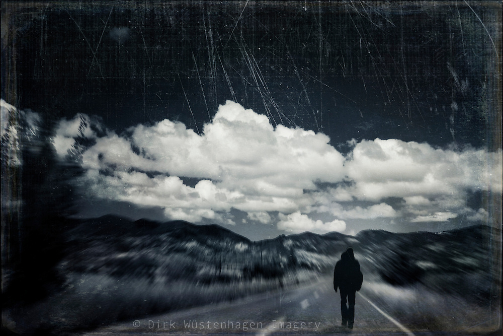 Man walking on a country road - texturized black and white photograph.