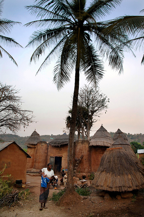 Natitingou December 2006 - A woman walks in front of his home in Natitingou, Benin.  The home is built in the Tata Somba architectural style.© Jean-Michel Clajot