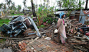 Woman standing in a monastry detroyed by Cyclone Nargis.