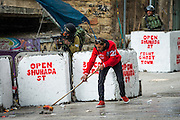 Palestinian peace activist Izzat Karake sweeps the street while an Israeli sniper aims his gun at a group of Palestinian children throwing stones nearby.