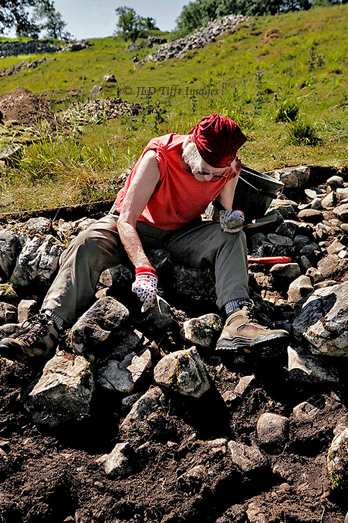 Woman in red shirt and cap concentrates on digging through a rock pile in an excavation site at Chapel House Wood, Wharfedale, Yorkshire.  Moor visible beyond the excavation site.