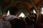 A crowd of people inside an inflatable church,  Boomtown, Matterley Estate, Alresford Road,  Winchester, Hampshire, UK, August, 2010