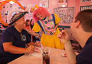 "Crystal makes Skip Beaver, left, and his son Travis laugh while she shows them a few card tricks. ""A clown is a catalyst, a little bit of something that makes you think, makes you feel, makes you see,"" Crystal said."