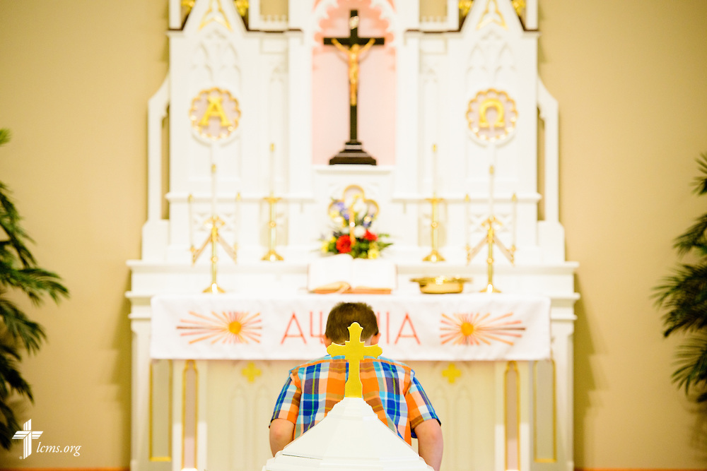 Acolyte Jonathan Jones bows at the altar after extinguishing candles at St. Paul Lutheran Church-Dewberry on Sunday, April 10, 2016, in Cross Plains, Ind. LCMS Communications/Erik M. Lunsford