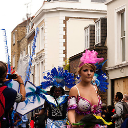 London, UK - 27 August 2012: a party-goer takes part at the parade during the Notting Hill Carnival while people party on the rooftop of a house.
