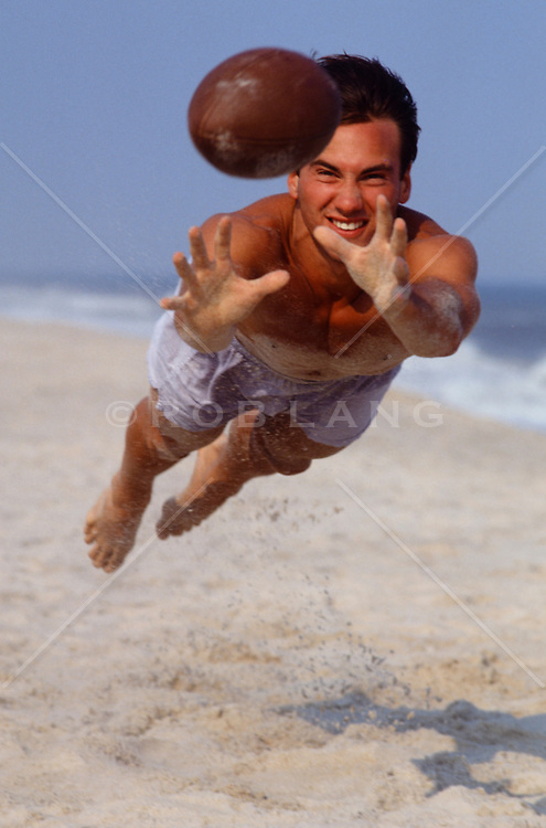 man catching a football in midair at the beach