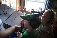 Lucas (5 ) and  McKenzie (6) shows his FAST program work at home in Shefield UK Tuesday, Aug. 12, 2014The D'Arby family is involved in the FAST  (Families and Schools Together) program which encourages parents to read to their children at home.(Elizabeth Dalziel for Save the Children )