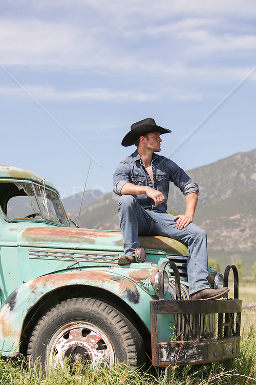 sexy young cowboy with an old pick up truck on a ranch