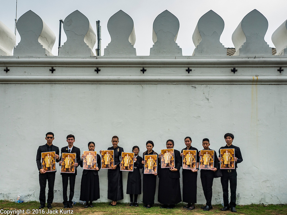 29 OCTOBER 2016 - BANGKOK, THAILAND:  People stand in front of the wall of the Grand Palace and hold up their portraits of the late Bhumibol Adulyadej, the King of Thailand, after they paid homage to His Majesty. Saturday was the first day Thais could pay homage to the funeral urn of the late Bhumibol Adulyadej, King of Thailand, at Dusit Maha Prasart Throne Hall in the Grand Palace. The Palace said 10,000 people per day would be issued free tickerts to enter the Throne Hall but by late Saturday morning more than 100,000 people were in line and the palace scrapped plans to require mourners to get the free tickets. Traditionally, Thai Kings lay in state in their urns, but King Bhumibol Adulyadej is breaking with tradition. His urn reportedly contains some of his hair, but the King is in a coffin,  not in the urn. The laying in state will continue until at least January 2017 but may be extended.      PHOTO BY JACK KURTZ